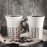 Two coffee cups. Two modern espresso cups on a wooden table Royalty Free Stock Image