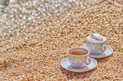 Two Coffee Cups at Sea Shore. Two coffee cups, Espresso and Cappucino at the Sea Shore on the Beach Stock Image