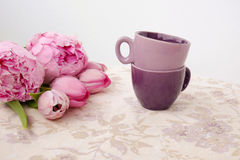Two coffee cups on a table. Two coffee cups and rose tulips and roses an a table Stock Photo