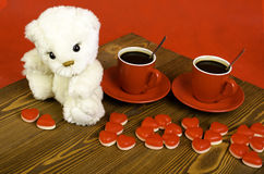 Two coffee cups, teddy bear and the word Stock Photo