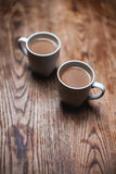 Two coffee cups. Two white coffee cups on the wooden table Royalty Free Stock Photo