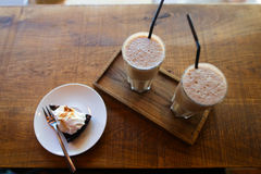 Two coffee drinks with drinking straw and slice of pie on saucer Royalty Free Stock Photography