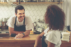 Two coffee house partners speaking in cozy cafe Stock Photos