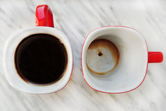 Two coffee mug, one empty, one full of coffee. Two coffee mug on marble top, one empty, one full of coffee Stock Photography