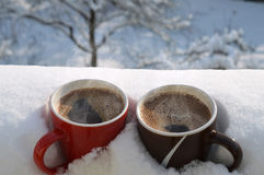 Two coffee mugs in snow. Foreground with two cups of hot steamy coffee buried in snow, just waiting two sleepy people to come and enjoy them, on a sunny winter Stock Image