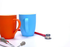 Two coffee mugs and a stethoscope Stock Images