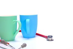 Two coffee mugs and stethoscope Stock Photos