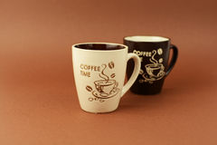 Two coffee time cups on brown background.  Stock Photo