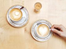 Two coffees and some sugar, please!. Two coffees on a wooden table seen from above. A woman& x27;s hand holds one of the cups while waiting for her partner Royalty Free Stock Photography