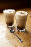 Two coffees and a spoon. The morning coffee with steamed milk in glass cups on a wooden bench Stock Photos