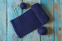Two coils of wool, knitting needles and a blue knitted scarf Stock Photos