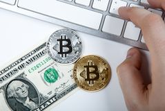 Two coins of bitcoin and a dollar bill and human hand on laptop Stock Image