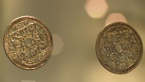 Two coins in museum. Steady, medium close up shot of two coins in a museum stock video footage