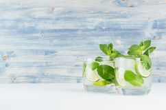 Two cold glasses with tropical cocktail mojito and straw on soft shabby blue wood board, copy space. Two cold glasses with tropical cocktail mojito and straw on Royalty Free Stock Photos