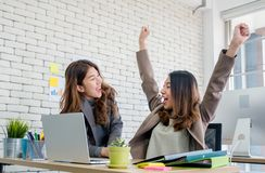 Two colleague businesswoman arms up for good news from job on la. Ptop about work at office.Digital business lifestyle concept royalty free stock image