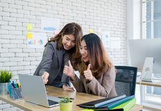 Two colleague businesswoman thumbs up for good job on laptop about work at office.Digital business lifestyle concept. Two colleague businesswoman thumbs up for stock photo