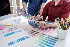 Two colleague creative graphic designer working on color selection and color swatches, drawing on graphics tablet at workplace. With work tools and accessories stock photo