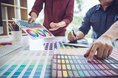 Two colleague creative graphic designer working on color selection and color swatches, drawing on graphics tablet at workplace. With work tools and accessories royalty free stock image