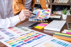 Two colleague creative graphic designer working on color selection and color swatches, drawing on graphics tablet at workplace. With work tools and accessories royalty free stock photos