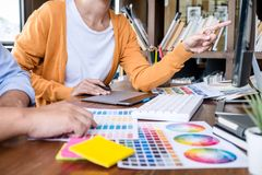 Two colleague creative graphic designer working on color selection and color swatches, drawing on graphics tablet at workplace stock images