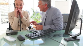 Two colleagues celebrating after a phone call. In an office stock footage