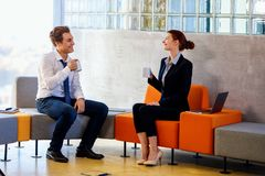 Two colleagues chatting on coffee break. Two colleagues chatting on coffee break in modern business center royalty free stock photography