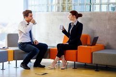 Two colleagues chatting on coffee break. Two colleagues chatting on coffee break in modern business center royalty free stock photos