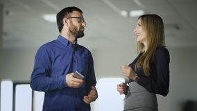 Two colleagues are chatting in the office during coffee break. Man in blue shirt is communicating with woman holding. Two colleagues are chatting in the office stock video footage