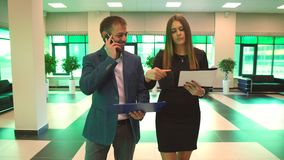 Two colleagues come to office and discuss business plan. In office stock video footage