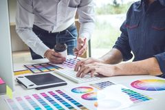 Two colleagues creative graphic designer working on color selection and drawing on graphics tablet at workplace royalty free stock photos