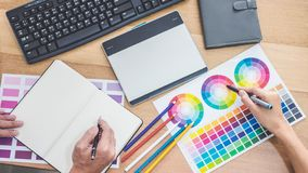 Two colleagues creative graphic designer working on color selection and drawing on graphics tablet at workplace, Color swatch. Samples chart for selection royalty free stock photography