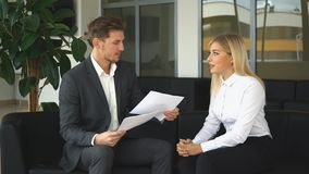 Two colleagues discussing business ideas sitting on the chairs in the office. Young businesswoman talking with a colleague about the business plan in office stock footage