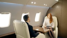 Two colleagues discussing business strategy of their company in private aircraft. Young businesswoman in white shirt, with red hair and notebook in her hands stock video
