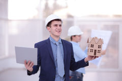 Two colleagues discussing data working and tablet, laptop with on on architectural project at construction site at desk Royalty Free Stock Photography