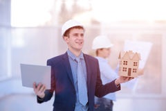 Two colleagues discussing data working and tablet, laptop with on on architectural project at construction site at desk Royalty Free Stock Images