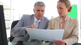 Two colleagues discussing information on a document. In an office stock footage