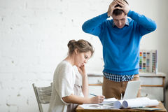 Two colleagues feeling troubled at work. Portrait of two coworkers arguing at work, having fight at modern office. Young stressed men holding his head in hands Royalty Free Stock Photos