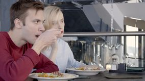 Two colleagues are having luch in restaurant together, slow motion. Blond woman in blue shirt is talking on her brand-new smartphone and man in red jumper are stock video
