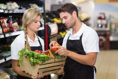 Two colleagues holding a box with fresh vegetables. At supermarket Royalty Free Stock Images