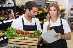 Two colleagues holding a box with fresh vegetables and writing on notepad Royalty Free Stock Images