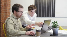 Two colleagues look information using internet in the laptop in office. stock video footage