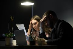 Two colleagues looking at bad company report in evening meeting. Two colleagues looking at bad company report in late evening meeting. Man and women holding Royalty Free Stock Photo