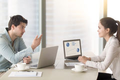 Two colleagues or partners discussing business issues sitting wi Stock Photos