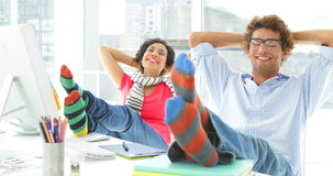 Two colleagues reclining on their swivel chair. In creative office stock video footage