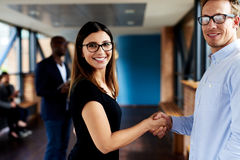Two colleagues shaking hands and smiling at camera Royalty Free Stock Image