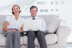 Two colleagues sitting on couch using laptop in bright office Royalty Free Stock Photography