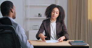 Two colleagues sitting in office meeting, Afro American business woman giving report to boss businessman finds error