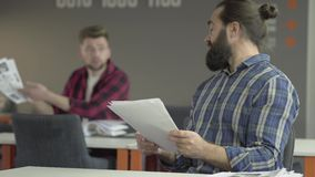 Two colleagues sitting in office studying new working information from papers. Young man in the background asking advice. Of bearded older co-worker but he is stock video footage