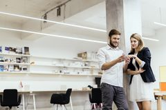 Two colleagues smiling while looking at the phone in an office. Two colleagues smiling while looking at the phone in a beautiful office royalty free stock photo