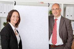 Two colleagues standing next to white flipchart Royalty Free Stock Images